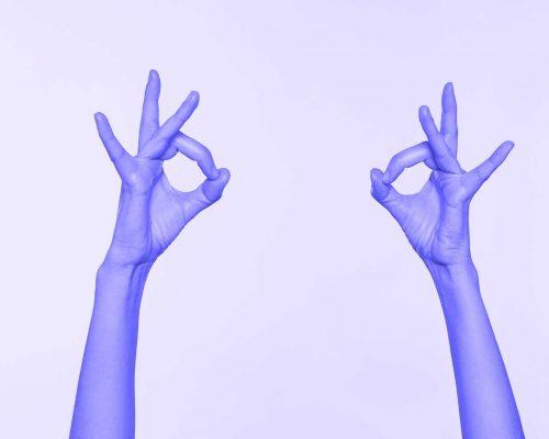 Aparecen unas manos realizando el signo de